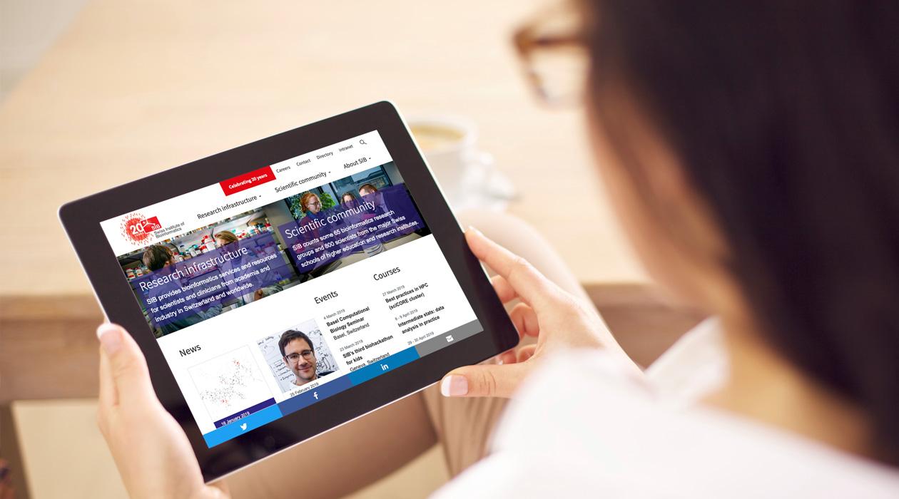 Femme avec des lunettes qui tient entre ses mains une tablette en regardant la page d'accueil du Swiss Institute of Bioinformatics